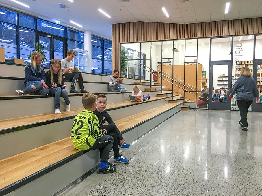 Endre, Erik Sebastian, Karen, Linnea, Ivar, Serine og Tiril i stor-amfiet, vi ser biblioteket i bakgrunnen.