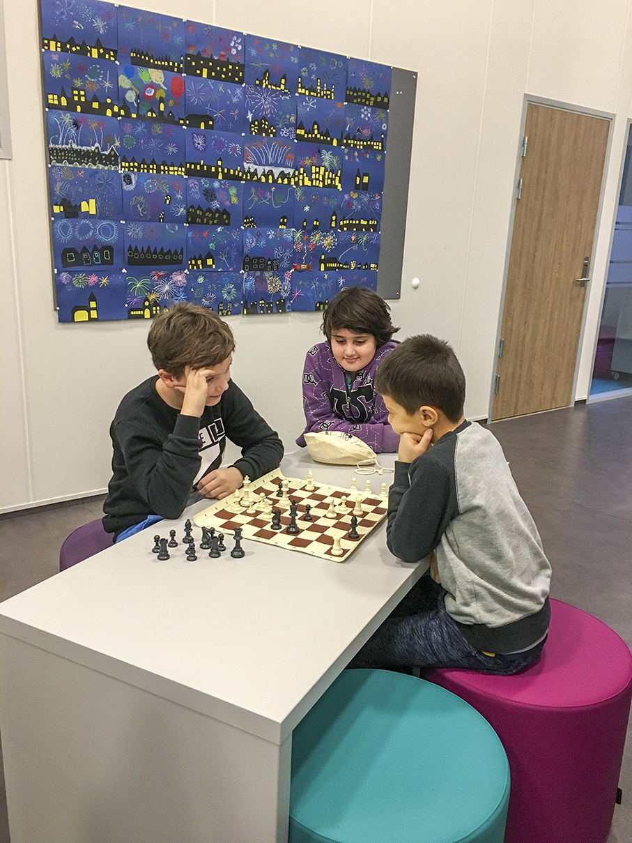 Andreas, Ahmed og Ferdous spiller sjakk i trinn-området.